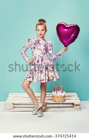 sweet little girl in a nice dress with birthday cake and pink balloon over turquoise wall - stock photo