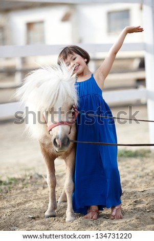 Sweet little girl in blue dress with her white pony