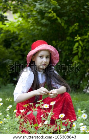 Sweet little girl in the rose garden.She picks oil rose for aroma therapy or perfumes