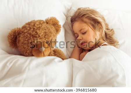 Sweet little girl is sleeping with her teddy bear in bed at home - stock photo