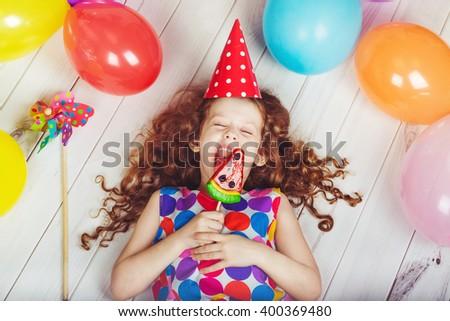 Sweet little girl licking a lollipop. - stock photo