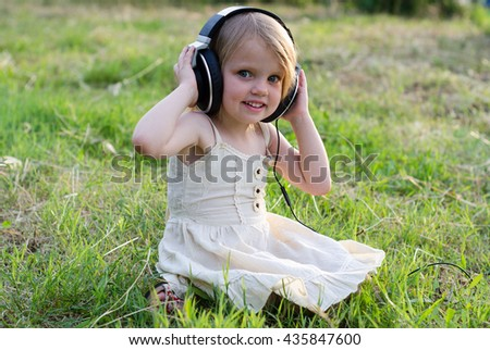 Sweet little girl listening music in headphones. - stock photo