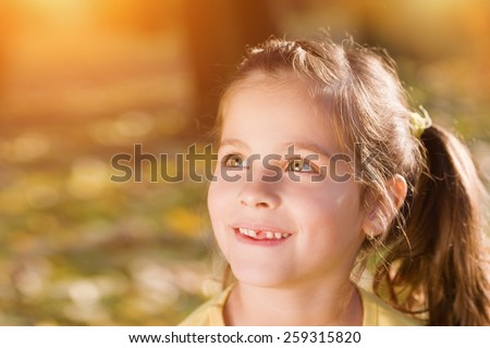 Sweet, little girl missing one front teeth smiling and looking away.Autumn season, shallow doff, sunset light, lens flare - stock photo