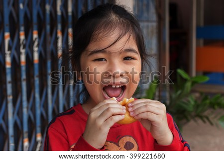 Sweet little girl outdoors with a eating donuts