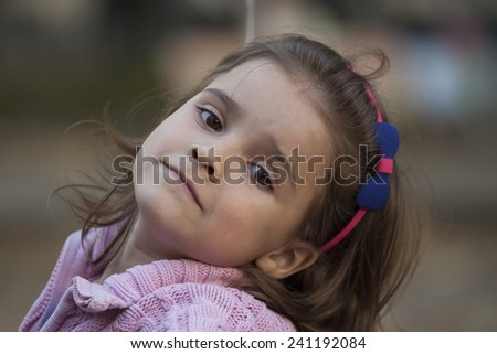 Sweet little girl outdoors with curly hair in the wind - stock photo