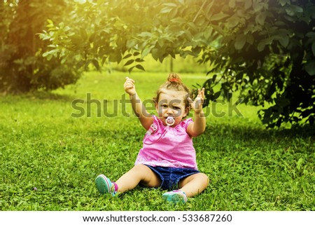 Sweet little girl outdoors with curly hair sitting on the grass