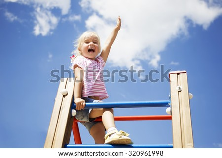 Sweet little girl outdoors with their hands raised sitting on the stairs against the blue sky - stock photo
