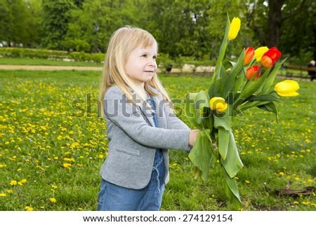 Sweet little girl outdoors with tulips - stock photo
