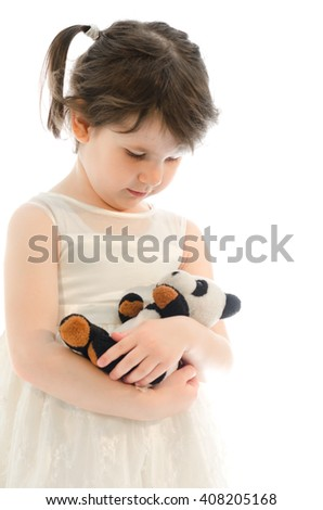 Sweet little girl playing with her teddy bear bedding him isolated on white background