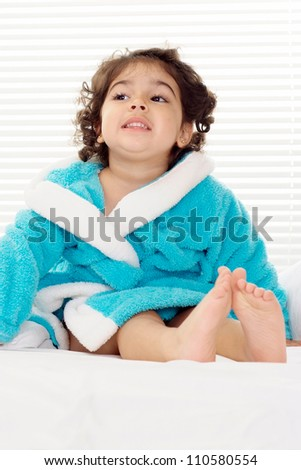 Sweet little girl resting at home on a white background