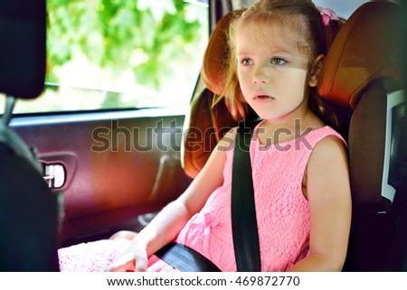 sweet little girl sitting in the car seat