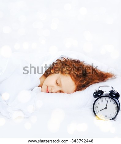 Sweet little girl sleeping in bed with a clock. Medical and healthy lifestyle concept. - stock photo