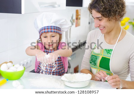 Sweet little girl sprinkle flour in kitchen