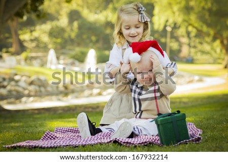 Sweet Little Girl Tries to Put A Santa Hat On Her Reluctant Baby Brother Outdoors at the Park.  - stock photo