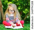 Sweet little girl wearing glasses and reading book in a park  - stock photo