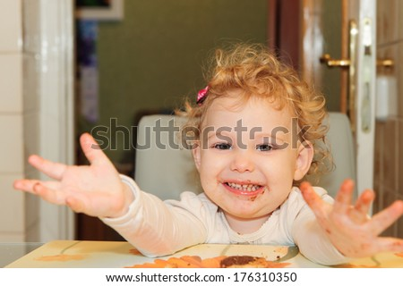 Sweet little girl with dirty face eating cookie at home - stock photo