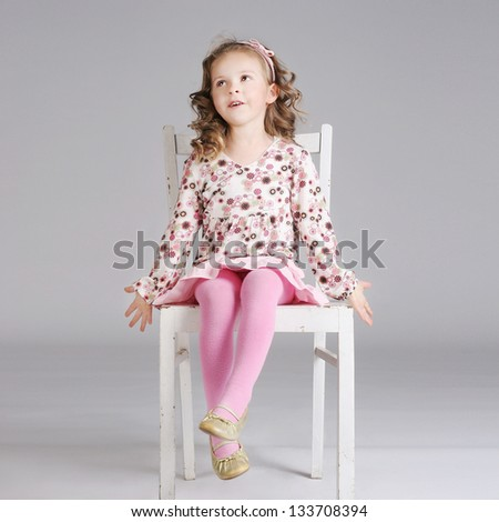 Sweet little girl with long curly hair posing in the white chair, looking away. - stock photo