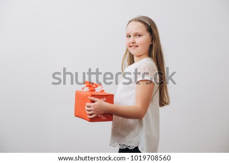Sweet little girl with present box as a gift for birthday on white background.Mother`s day.