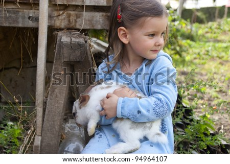 Sweet little girl 3 years old hugs her baby rabbit in the farm yard - stock photo