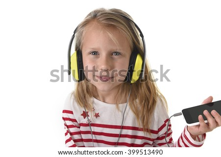 sweet little girl 7 years old with blonde hair and blue eyes listening to music with headphones and mobile phone giving enjoying song happy isolated on white background - stock photo