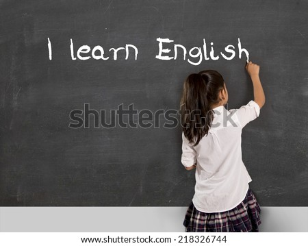 sweet little Hispanic girl at school lesson with ponytail and uniform writing with chalk on classroom blackboard in English learning , wisdom and successful education concept  - stock photo