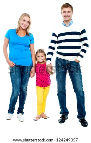 Sweet little kid standing in between her parents and holding their hands. Full length portrait
