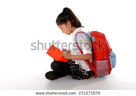 sweet little latin kid reading textbook or notepad smiling sitting on the floor with backpack in children education and back to school concept isolated on white background - stock photo