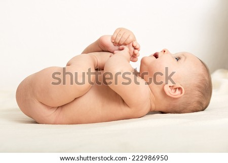 Sweet little 5 months old baby boy laying on his back and holding his feet in hands and looking up - stock photo