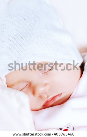Sweet little newborn baby sleeping in her bed.