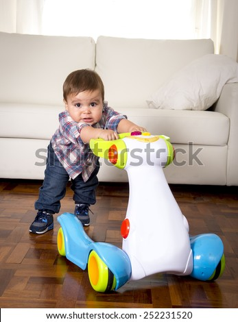 sweet little one year old boy walking alone with baby walker taking his first brave steps at home in living room excited and playful in childhood and growth concept - stock photo
