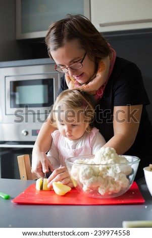 Sweet little one year old girl is learning from her mom how to cut potatoes in the home kitchen.