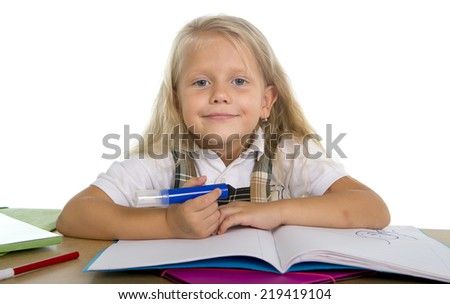 sweet little playful schoolgirl with blue eyes and blonde hair smiling happy having fun doing homework in children education concept isolated on white background