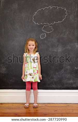 Sweet little schoolgirl with a thought bubble on blackboard looking at camera. Full length shot of caucasian young girl standing at home. - stock photo