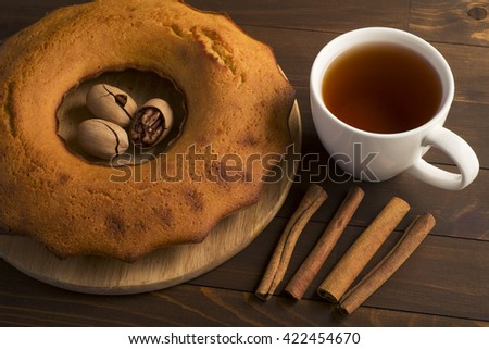 Sweet lush cupcake with tea. In white dish on wooden table