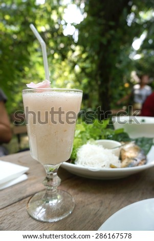 Sweet lychee frappe drinks on the dining table during meal with food background