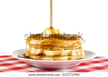 Sweet maple syrup being poured over a hot, freshly buttered stack of pancakes.