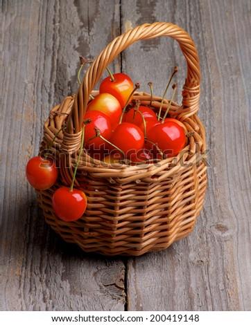 Sweet Maraschino Cherries in Wicker Basket isolated on Rustic Wooden background - stock photo
