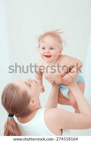 Sweet Maternity. Mother holding her baby in the air sending air kisses to the child while baby smiling happily  - stock photo