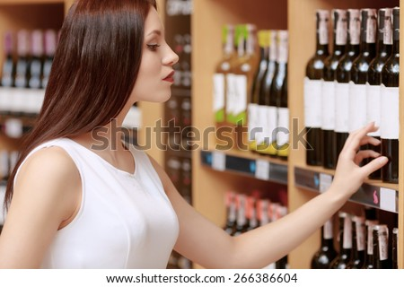 Sweet memories. Cropped shot of a young attractive woman touching with tips of her fingers label of the wine bottle in a liquor store - stock photo