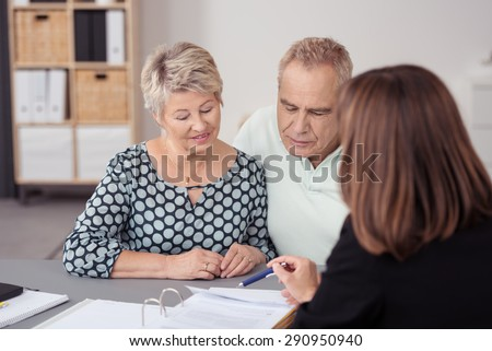 Sweet Middle Aged Couple Listening to a Female Business Agent Discussing to them What is on the Document at the Table. - stock photo