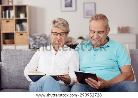 Sweet Middle Aged Couple Reading Something From Book and Tablet Computer While Relaxing at the Living Room Couch - stock photo