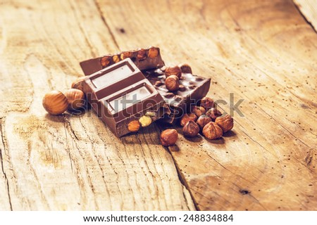 Sweet, milk chocolate with nuts on a wooden rustic table. - stock photo
