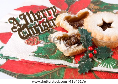 Sweet Mince Pies resting on christmas themed napkins - stock photo