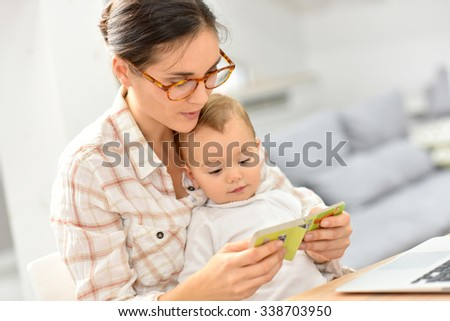 Sweet moment with mother reading book to baby  - stock photo