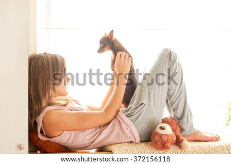 Sweet morning! Young girl in pyjamas holding her lovely Toy-terrier dog in rays of sunlight. Multicolored vibrant horizontal indoors image. - stock photo