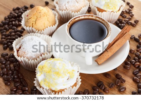 Sweet muffin and coffee on wooden background, tasty breakfast. Coffee beans. Closeup. - stock photo
