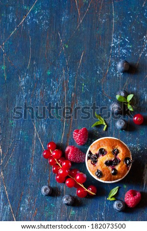 Sweet muffin surrounded by fresh berries with copy space for note or recipe.  - stock photo