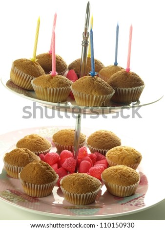 Sweet muffins with colorful birthday candles, isolated - stock photo