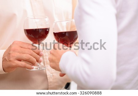 Sweet nectar. Close up of glasses in hands of loving adult couple holding them and drinking wine - stock photo