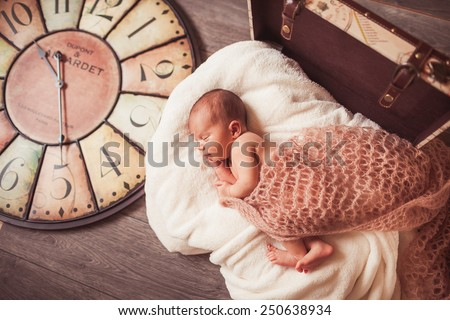 Sweet newborn baby. Big watch on baclground. Concept about time - stock photo